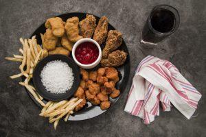 chicken-nuggets-fried-chicken-drumstick-crispy-chicken-popcorn-french-fries-with-softdrink-napkin-concrete-background_23-2148029606