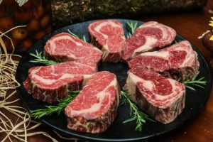 front-view-raw-marbled-meat-steak-with-rosemary-stand_141793-12208